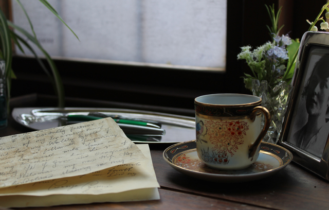 photograph, letter, cup and saucer, pens and flowers