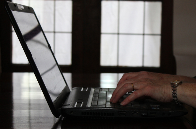 Hands typing laptop